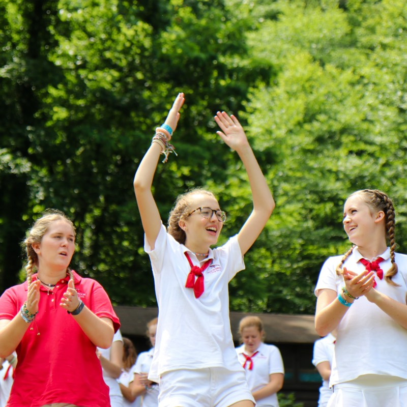 girls cheering at summer camp assemby