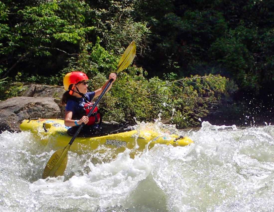small camp girl kayaking in rapid