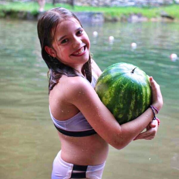 girl holding watermelon near the lake