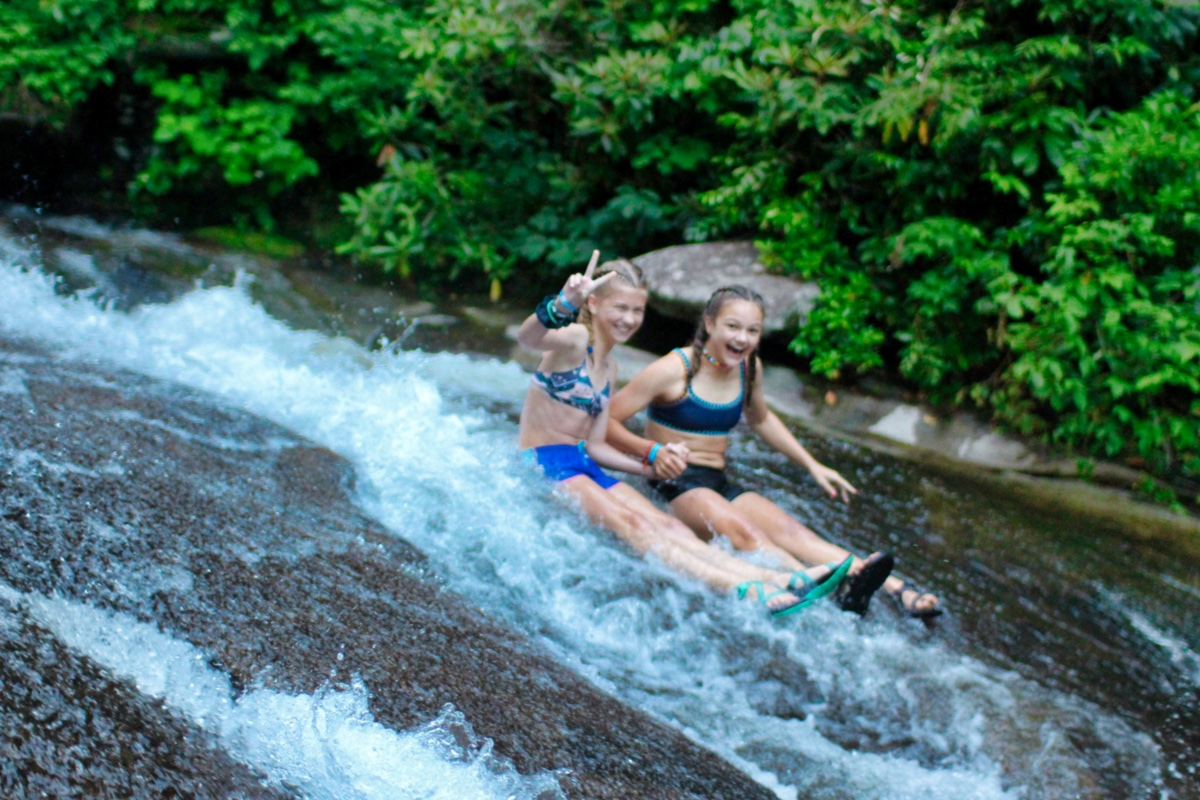 two girls sliding rock