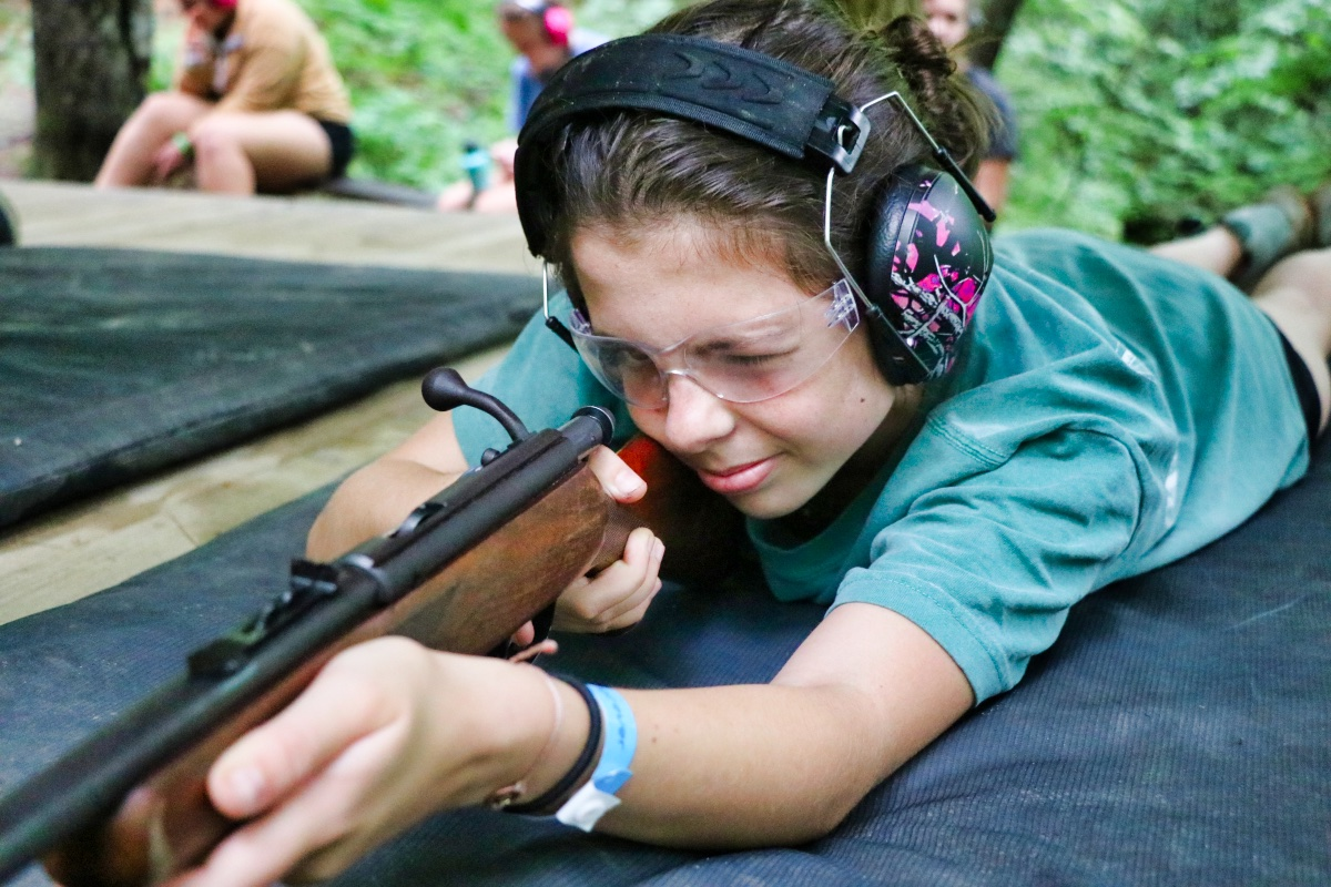 girls aiming rifle