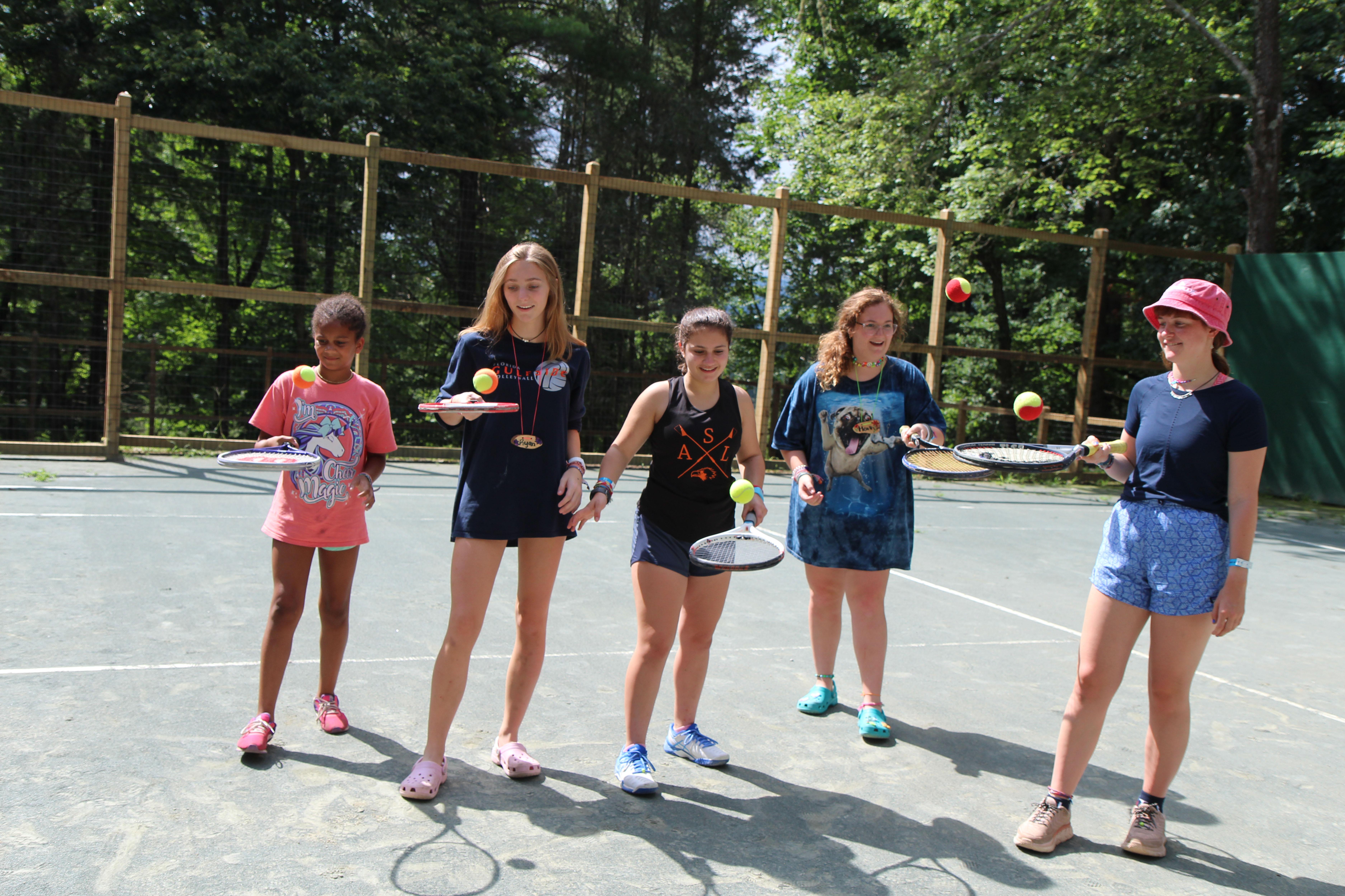 Girls at camp playing tennis
