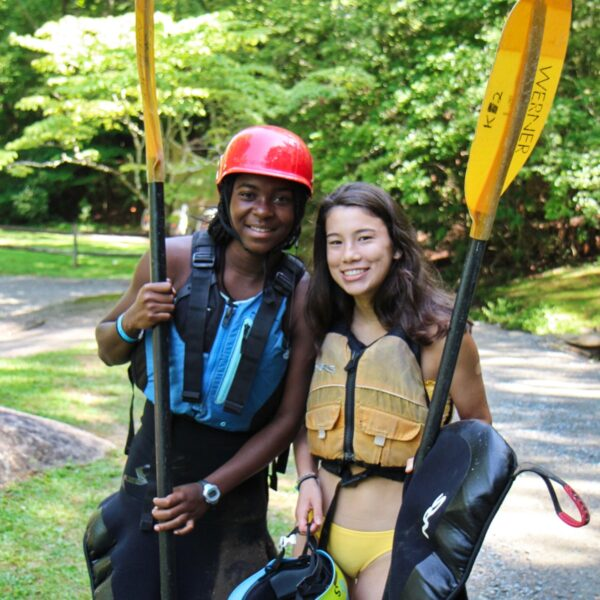 two camp girls dressed in kayaking gear ready for adventure