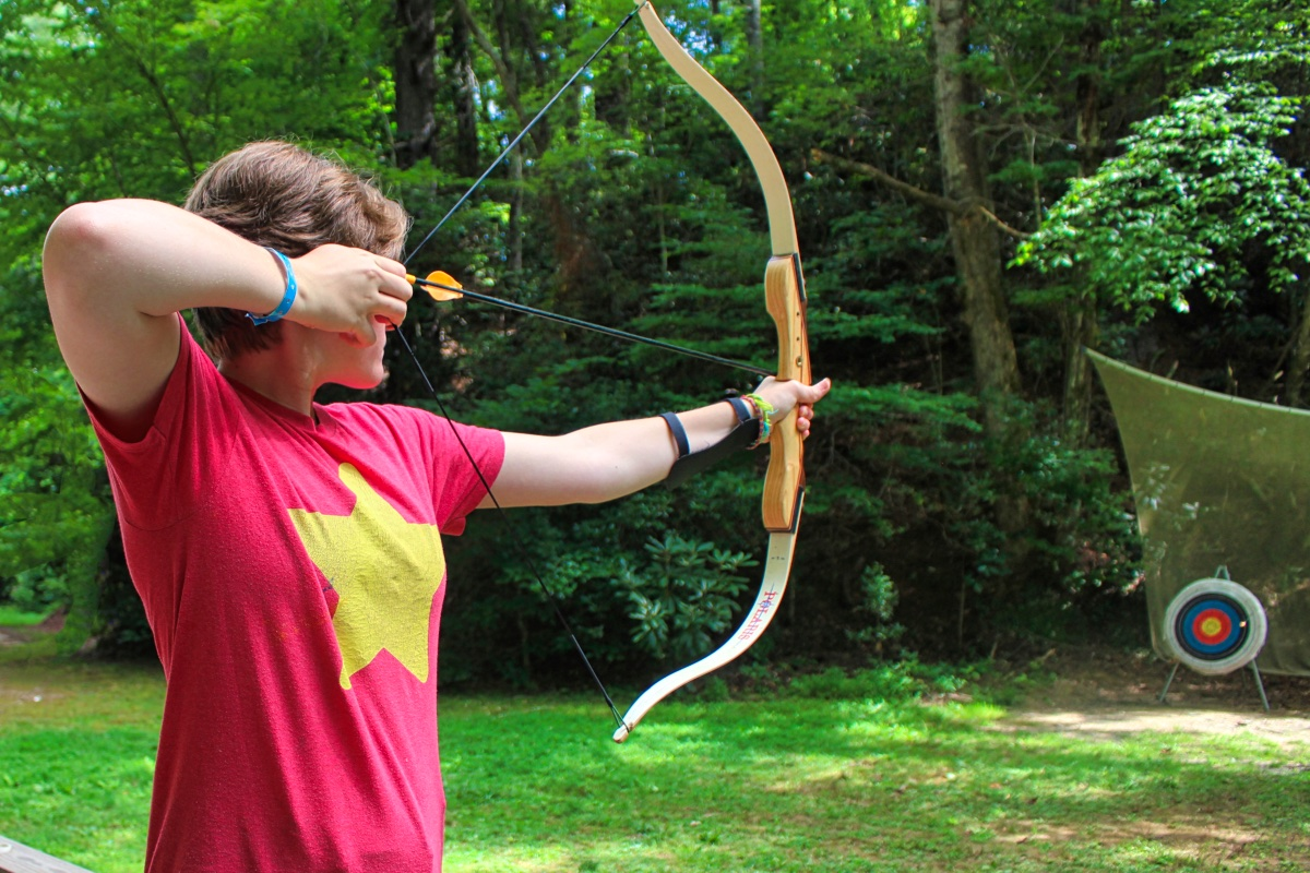 girl pulling back archery bow