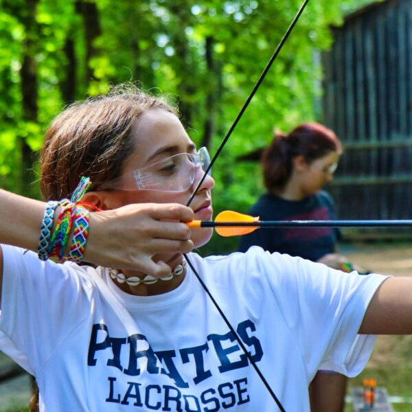 girls pulling back archery bow with bracelets on