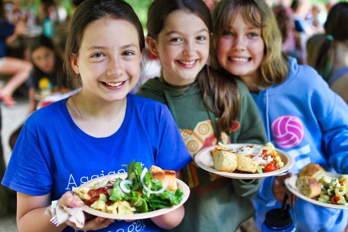 camp kids holding picnic dinner