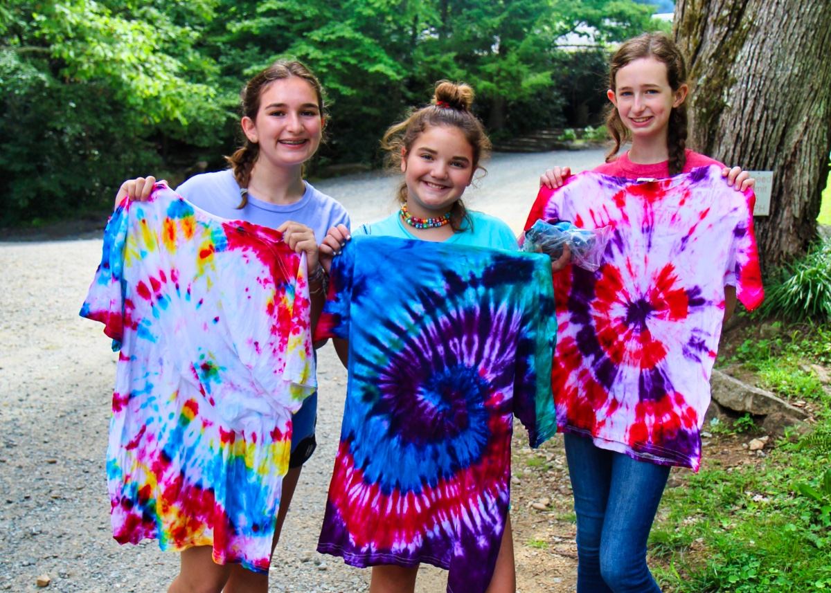 girls holding up tie-dye t-shirts they made