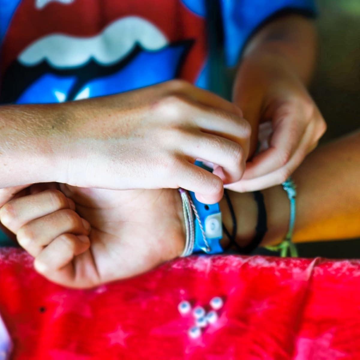tying a friendship bracelet on a wrist