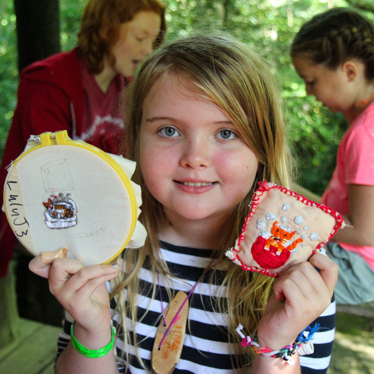 proud camp girl holding needlecraft projects