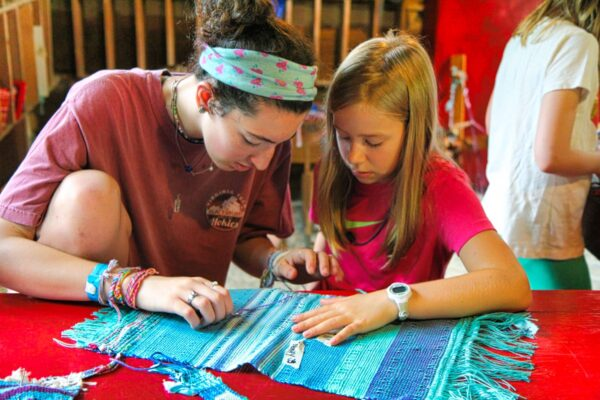 counselor and camper working on weaving