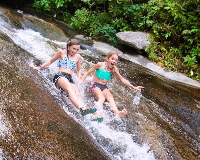 two teenage girl sliding down water
