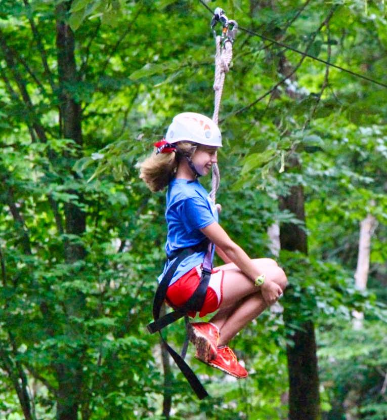 teen girl riding zipline at camp